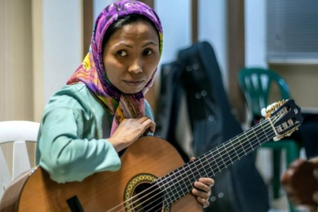 Maryam, 32, an Afgahn refugee in Iran, plays the guitar at the Sepahan Sina music centre in Esfahan.